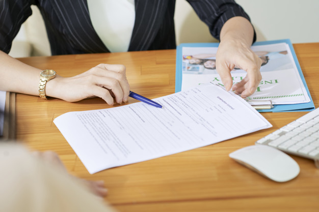 Insurance agent explaining woman what to write in contract